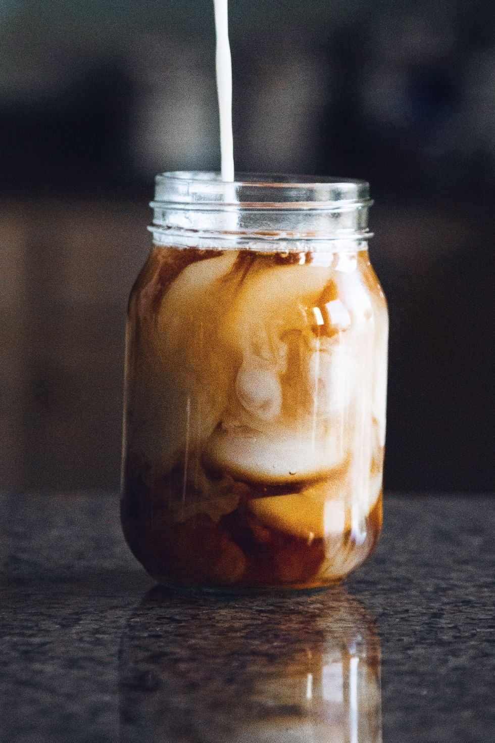 a mason jar with creamer being poured into the keto iced coffee