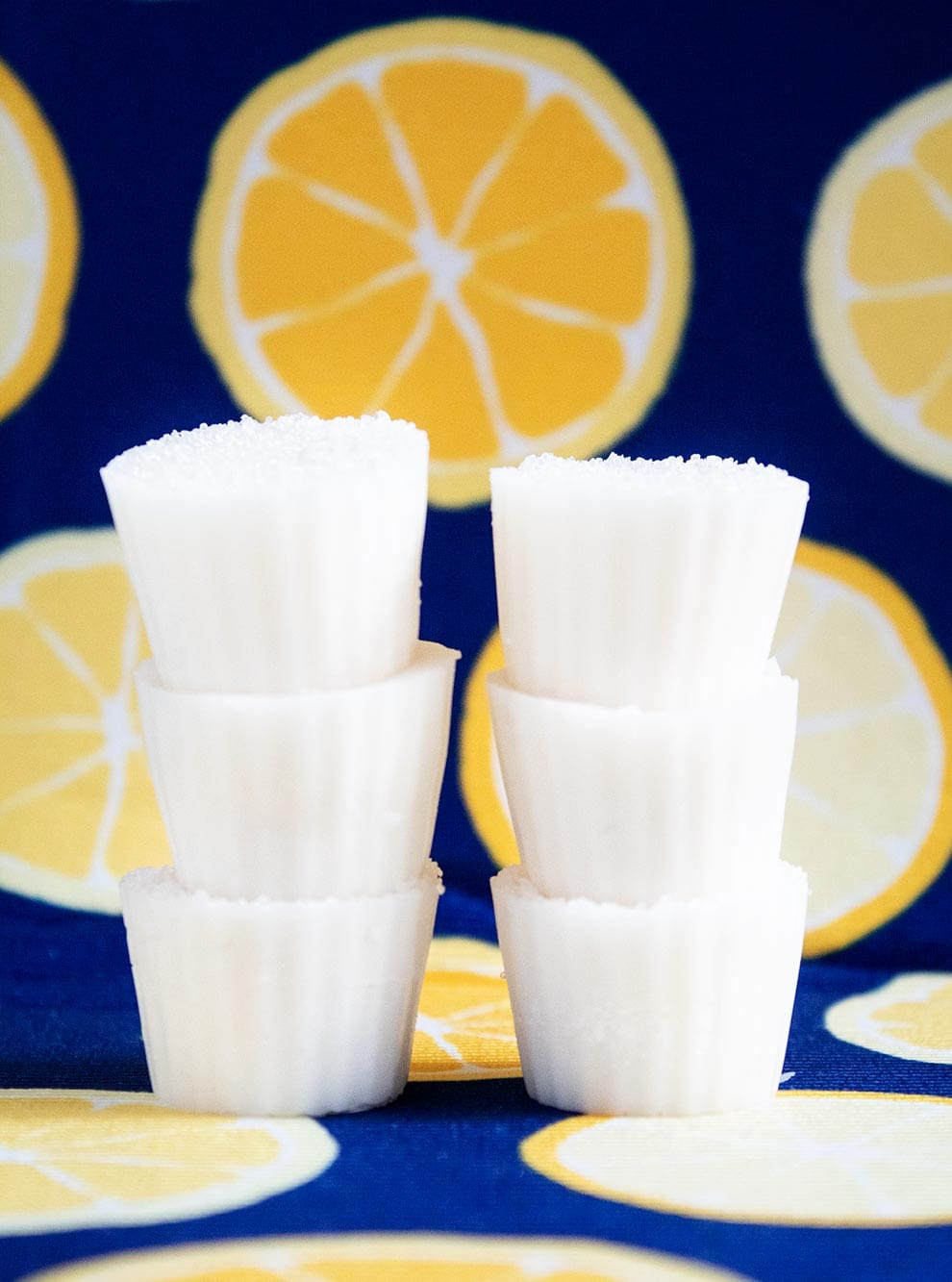 keto lemon coconut fat bombs stacked three high on a lemon and blue background