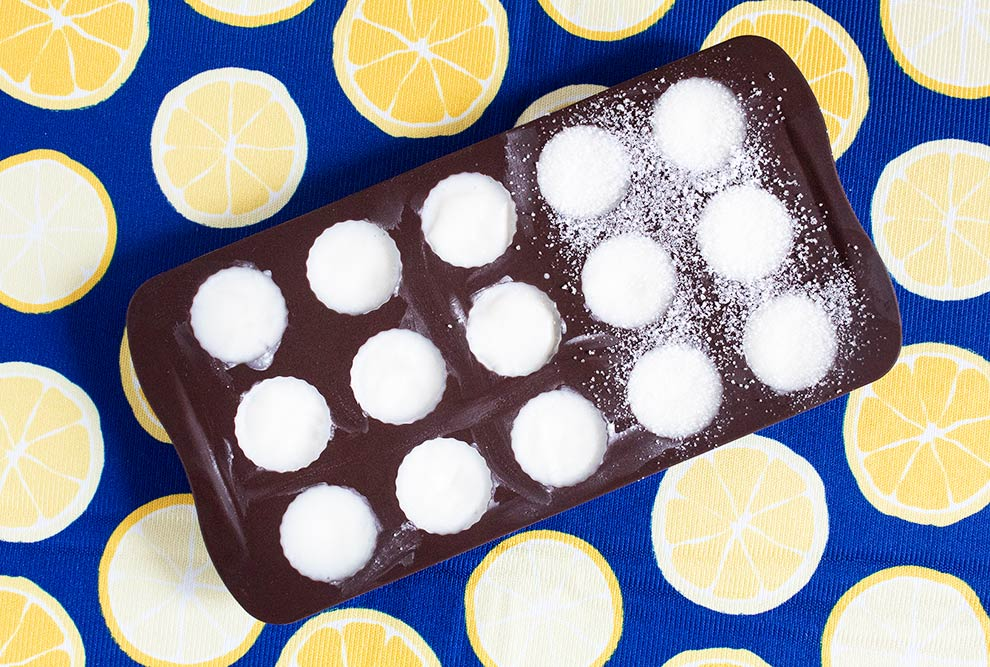frozen keto lemon coconut fat bombs in a brown mold on a bright lemon towel with blue