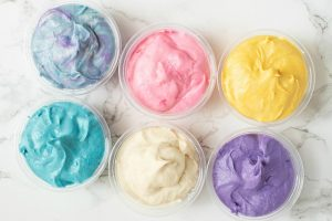 six keto frosting shots in multiple bright colors on a granite countertop