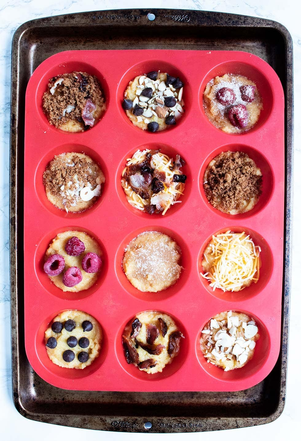 overhead view of keto pancake muffins with toppings before being baked
