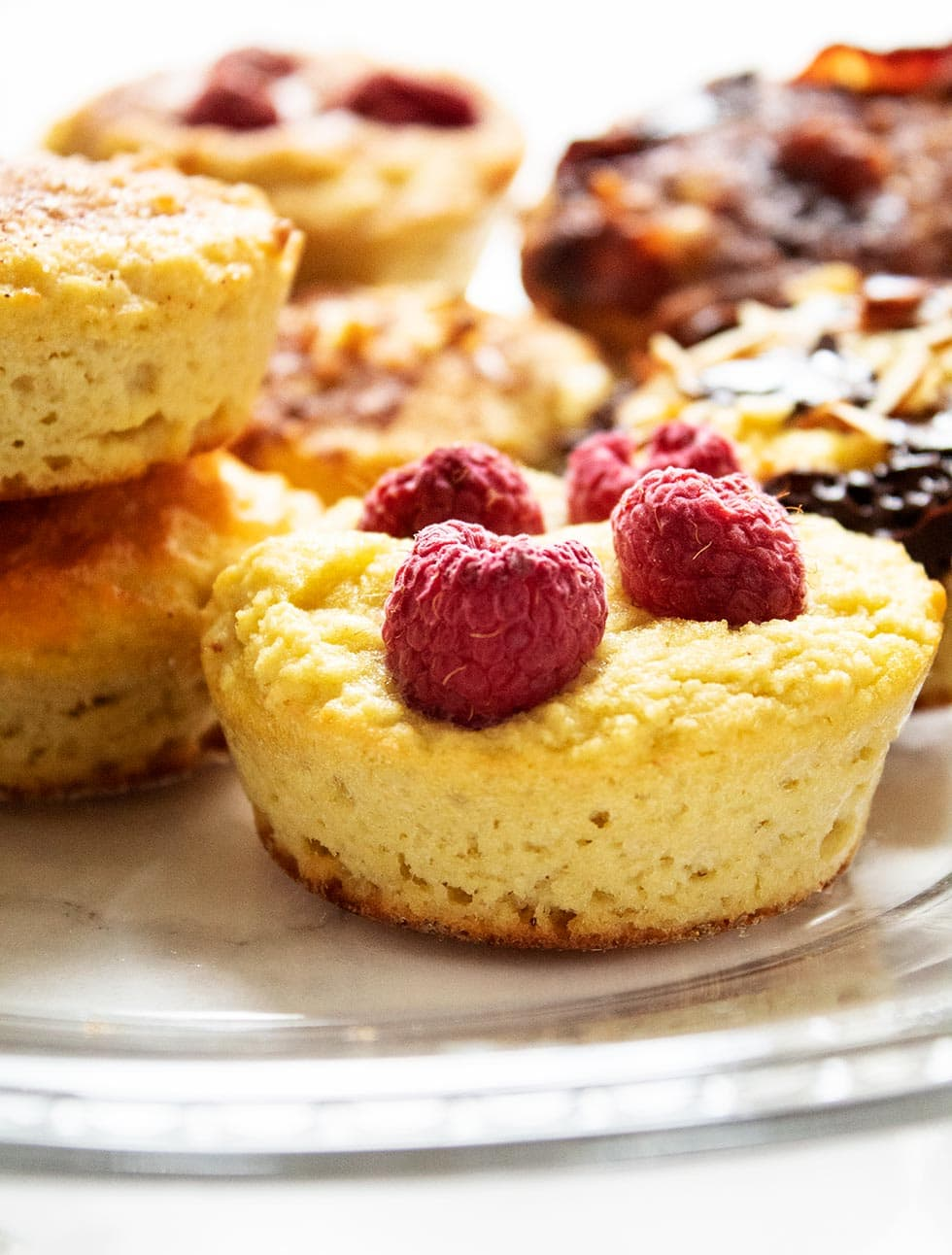 closeup of keto pancake muffins on a plate with toppings like raspberries