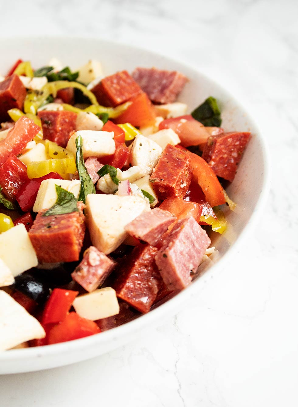 side view of a bowl containing keto antipasto with dressing