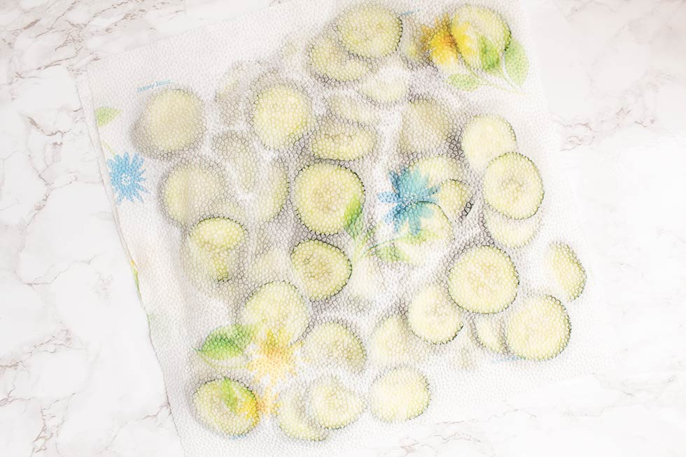paper towels covering cucumber slices to get out water
