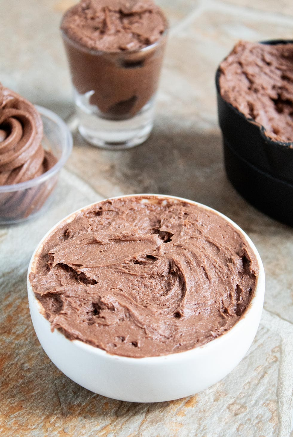 closeup of keto chocolate frosting in a white bowl with keto frosting in various containers behind it