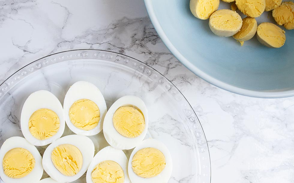 eggs with some yolks removed in a bowl to be used in keto deviled eggs