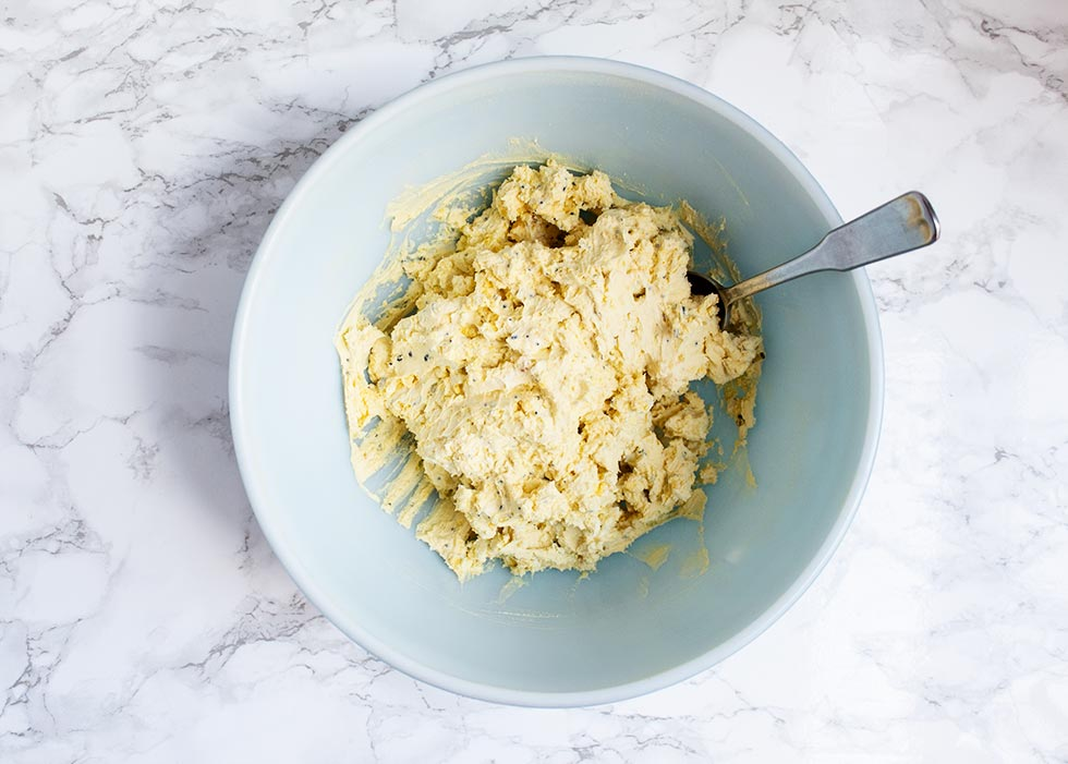 overhead view of keto deviled eggs mixture in a blue bowl with a spoon sticking out of the right side