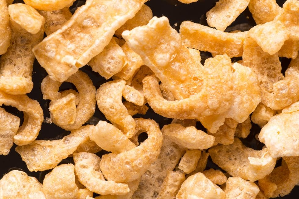 closeup of crunchy keto snacks pork rinds on a black background