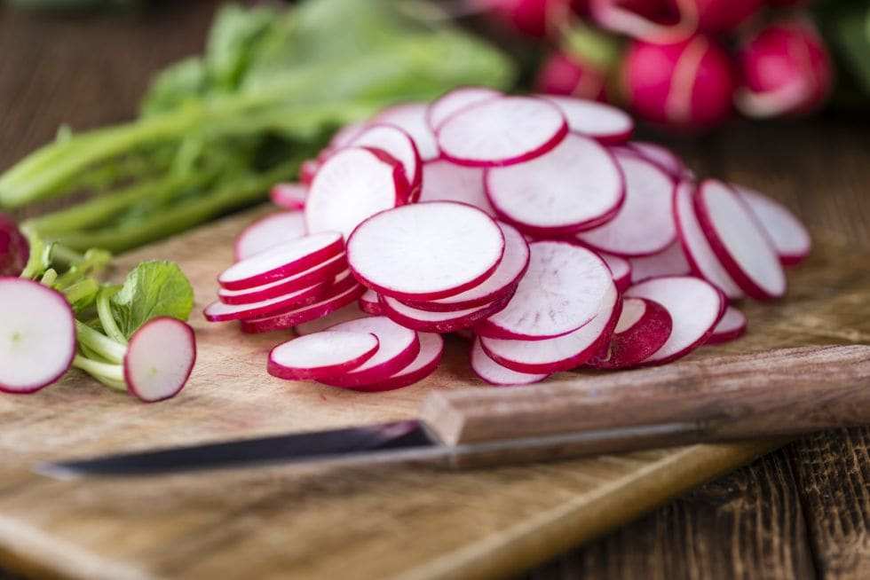 crunchy keto snacks with radishes sliced up on a cutting board next to a kife