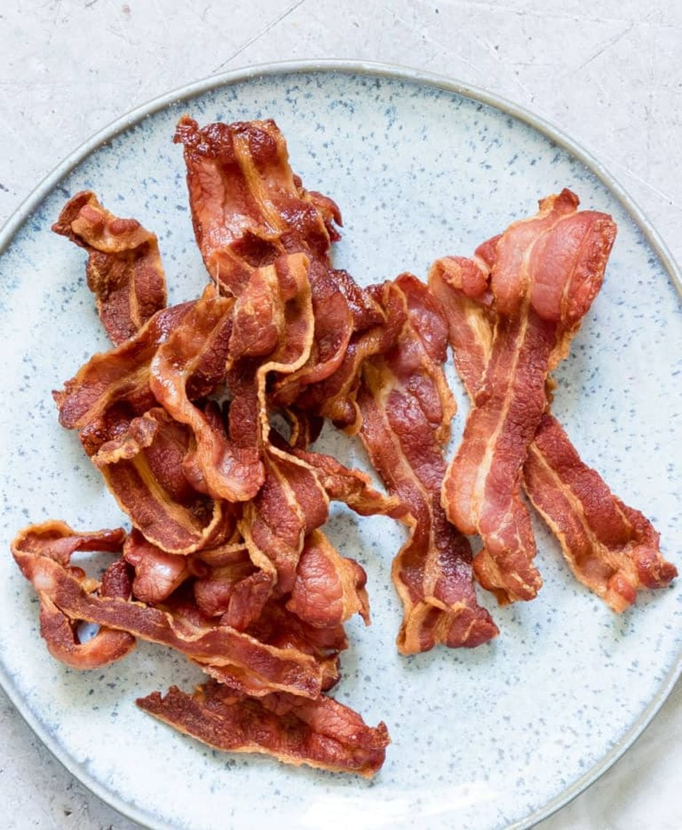strips of bacon on a blue platter as a crunchy keto snack