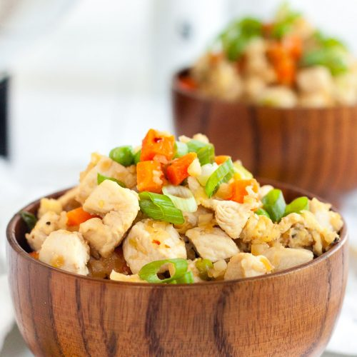 two bowls containing keto chicken fried rice mounded on top on a white background