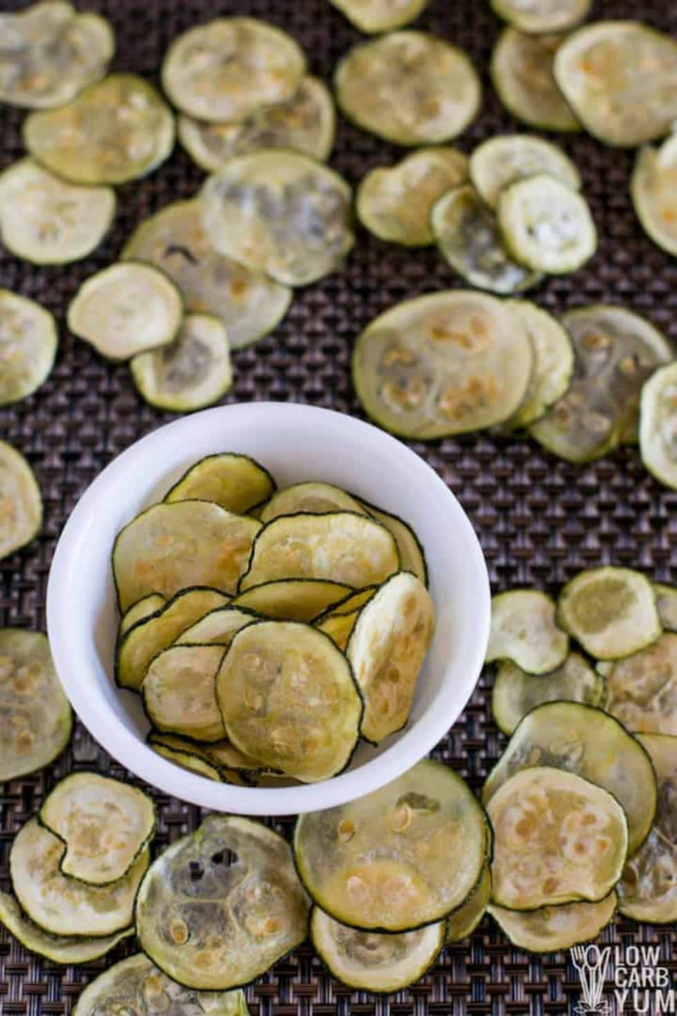 lots of crunchy keto snack zucchini chips spread across a table with a white bowl containing zucchini chips