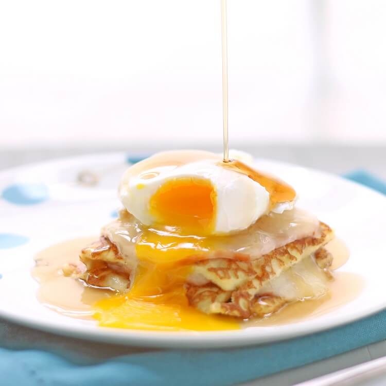 maple syrup being drizzled down on top of an egg over a slice of casserole