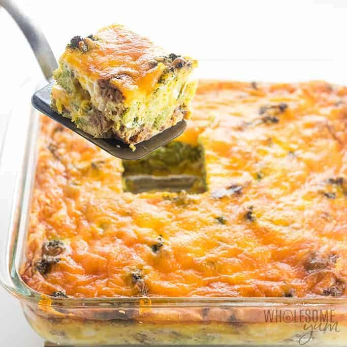 serving spoon scooping up a square piece of keto breakfast casserole over a clear casserole dish