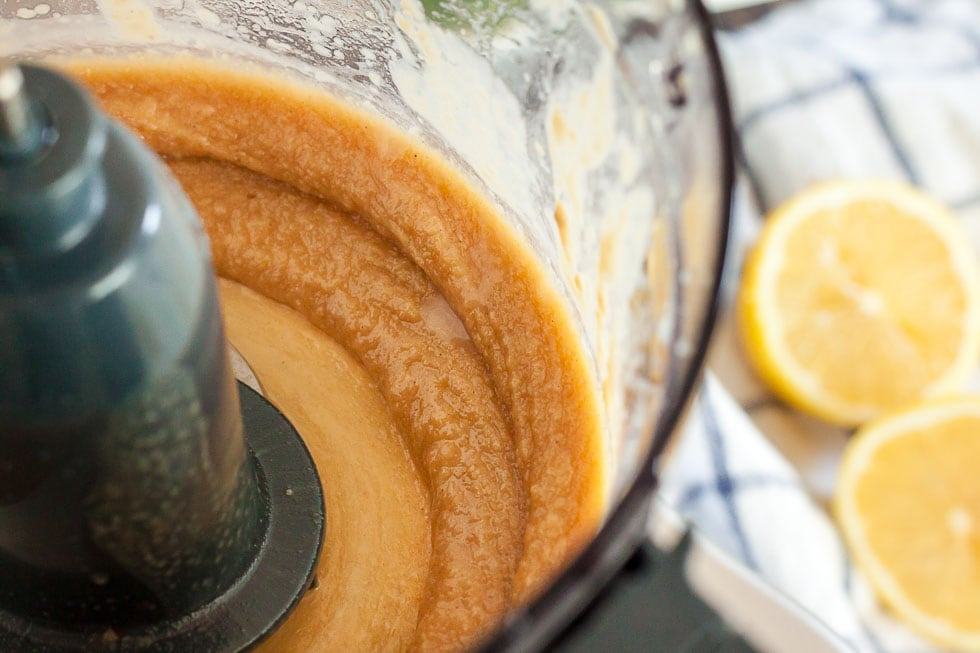 inside of food processor containing paste of lemon juice and tahini for keto hummus
