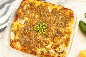 landscape pan of keto jalapeno popper dip with a towel in the upper lefthand corner