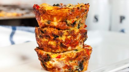 three keto mini quiches stacked high on a plate next to a salt and pepper shaker