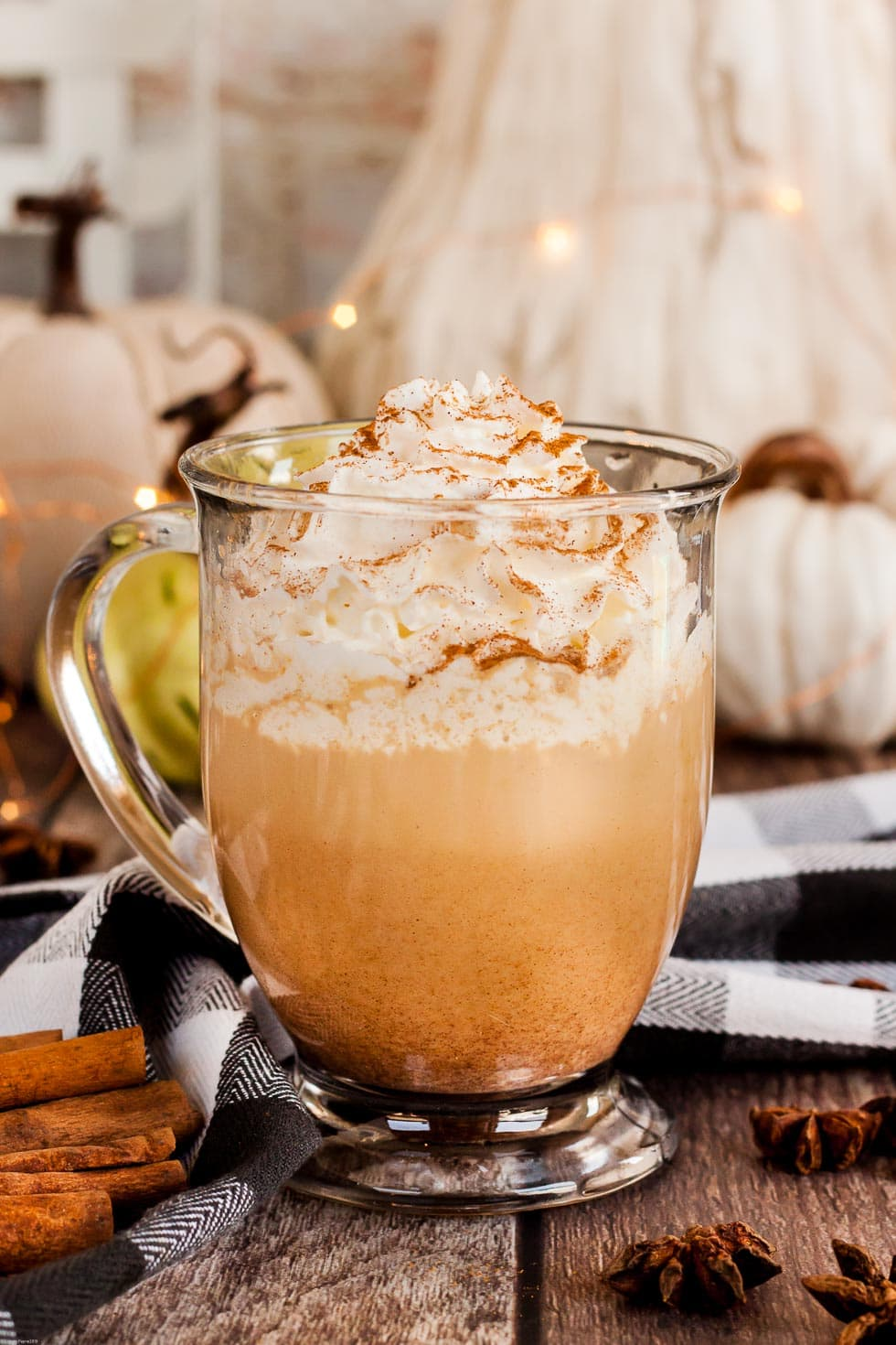keto pumpkin spice latte with whipped cream on top in front of a white and beige pumpkin