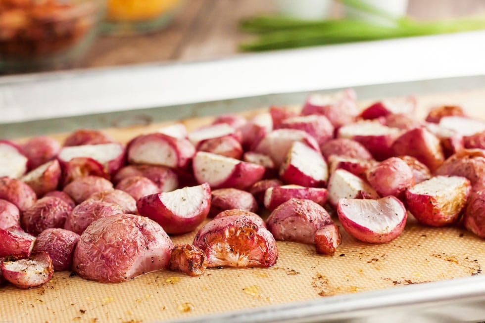 closeup of keto radishes that have been roasted sitting on a baking sheet