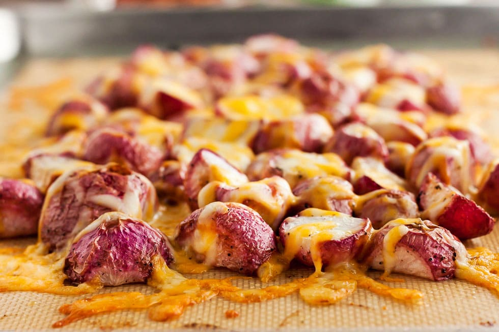 closeup of keto roasted radishes on a baking sheet covered with colby jack cheese
