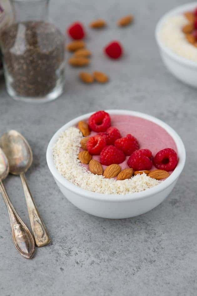 bowl containing keto breakfast ideas no eggs with raspberries and raw walnuts on top