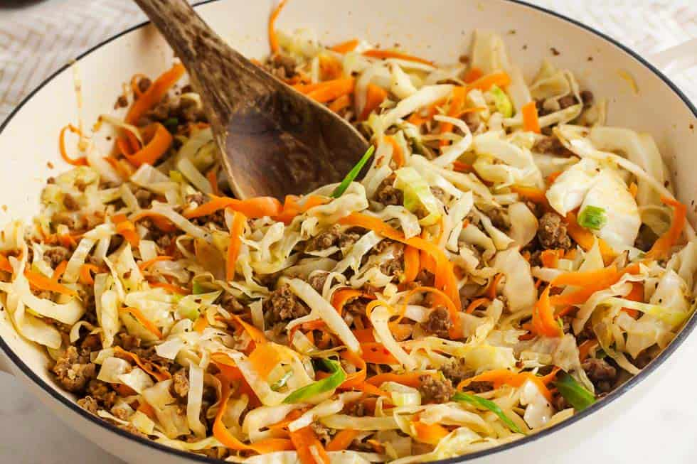 wooden spoon inside of a bowl containing cooked shredded cabbage with carrots and pork