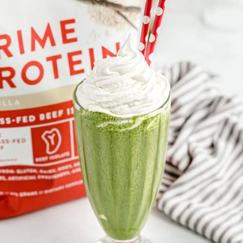 a keto shamrock shake with whipped cream on top and red and white straws