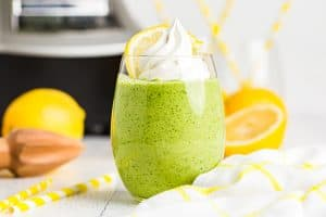 keto lemon smoothie topped with whipped cream in front of a blender