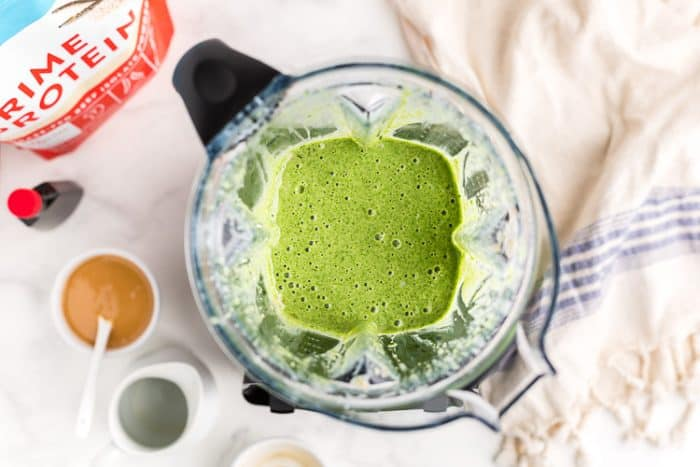 overhead view of a blender containing blended keto banana green smoothie