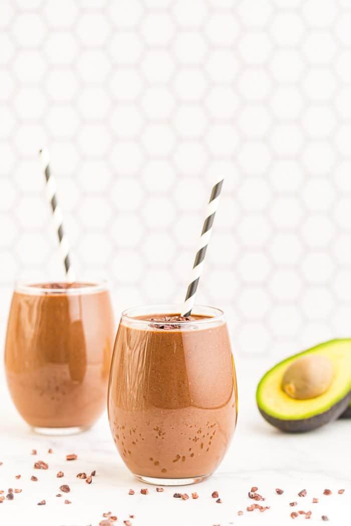 two keto chocolate smoothies with straws next to an avocado half