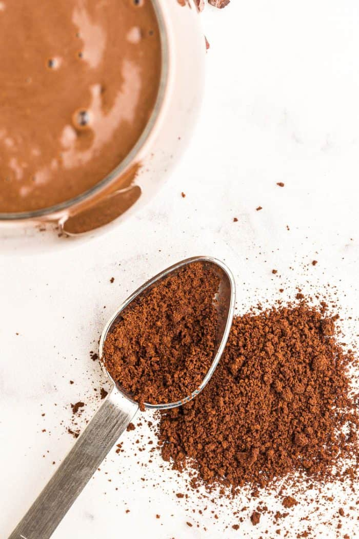 instant coffee granules on a spoon next to a smoothie