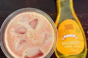 overhead view of keto starbucks refresher copycat next to a bottle of choczero mango