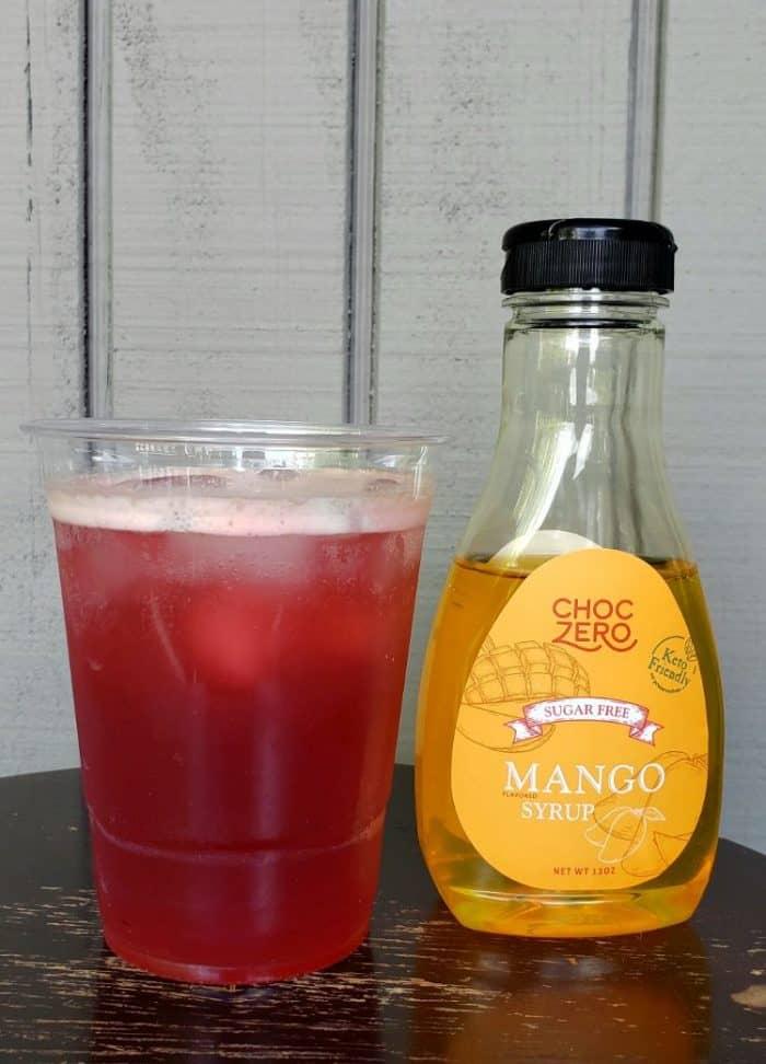 keto starbucks refresher in a glass next to choczero mango syrup