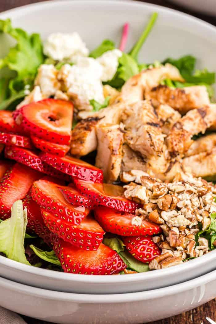 side view closeup of keto strawberry chicken salad with feta cheese and pecans on top