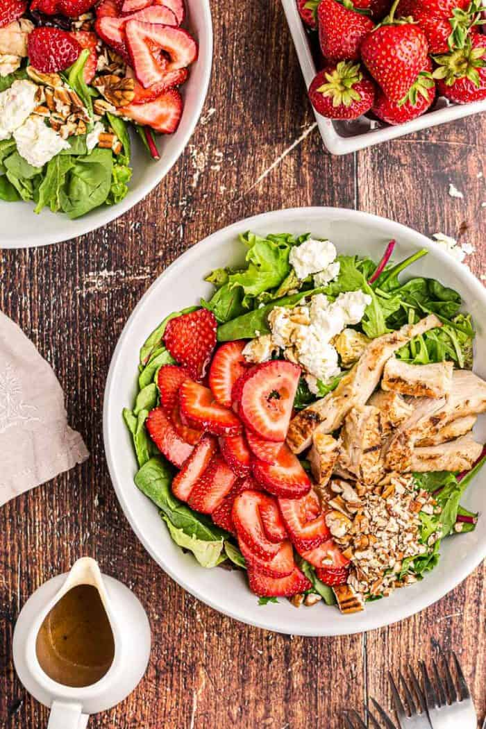 overhead view of keto strawberry chicken salad next to a bowl of fresh strawberries