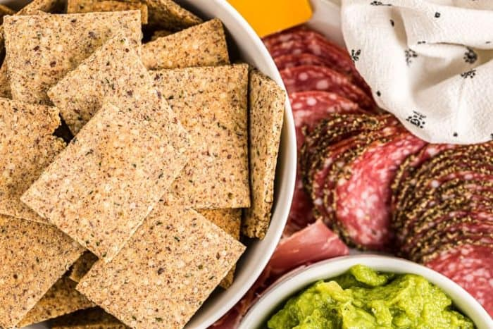 low carb crackers in a bowl next to meats and cheeses