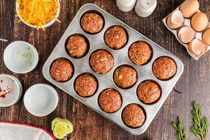 overhead view of keto meatloaf muffins in a pan surrounded by ingredients