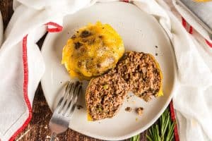 white plate containing two keto meatloaf muffins with cheese on top