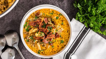 overhead view of a single bowl of keto cheeseburger soup by white towel