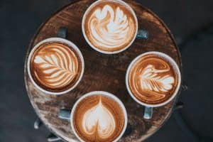 four cups of keto coffee with designs in the milk