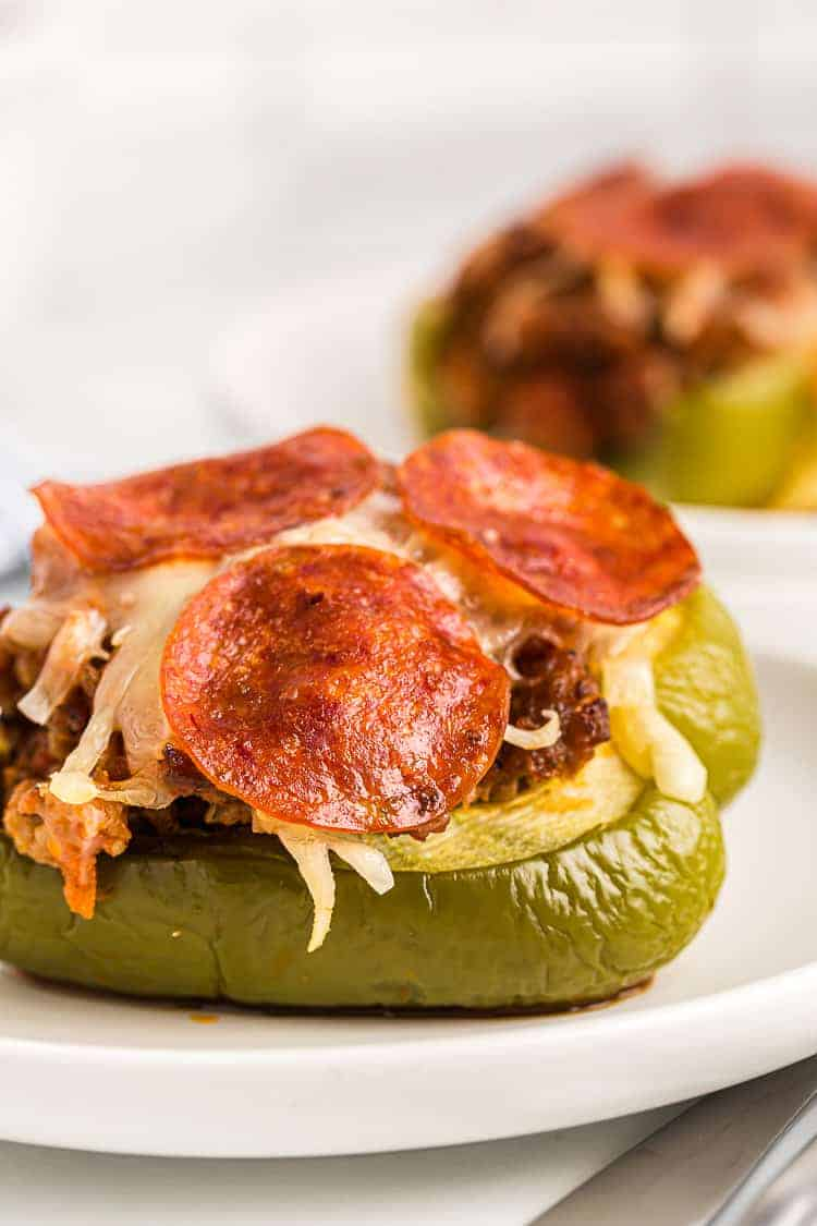 side view of keto stuffed bell peppers on white plates