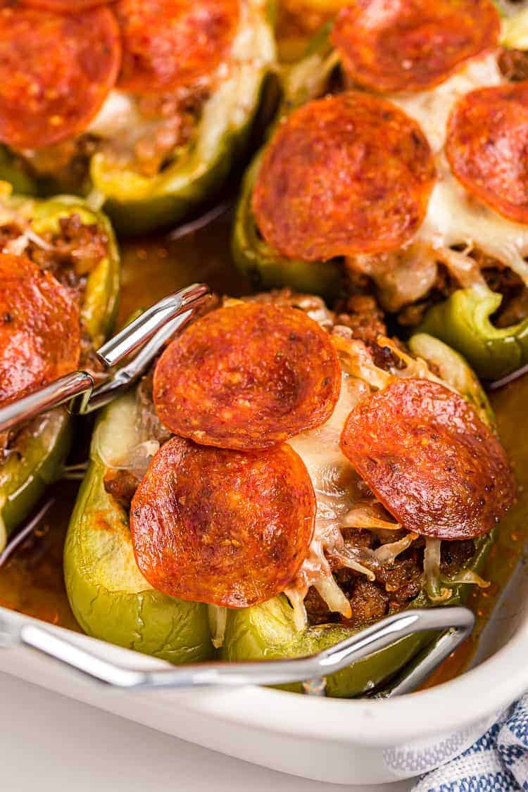 tongs reaching out for a piece of keto stuffed peppers with pepperoni on top