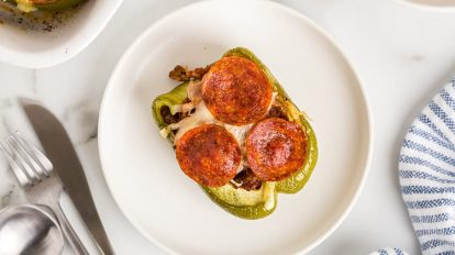 overhead view of single keto stuffed bell pepper on a white plate