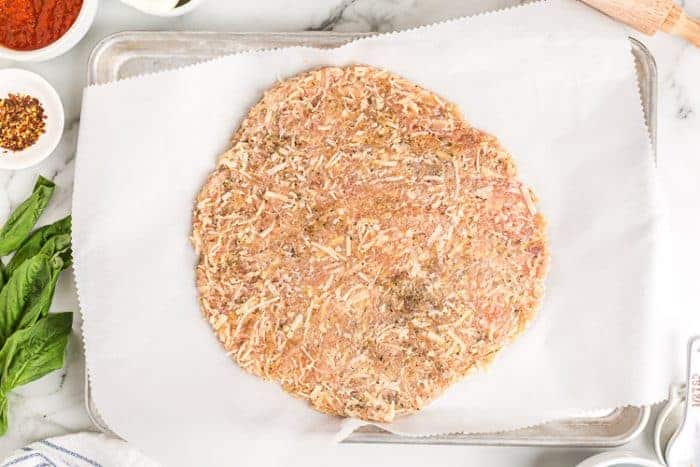overhead view of chicken crust pizza keto dough spread on cookie sheet
