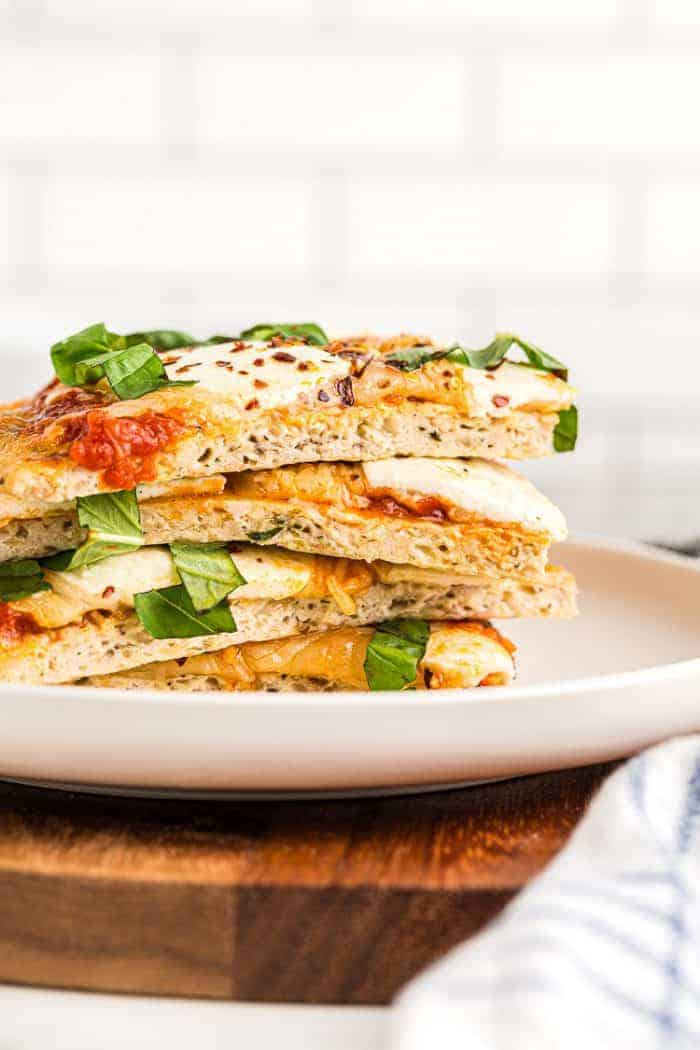 side view of sliced and stacked low carb chicken pizza crust pieces