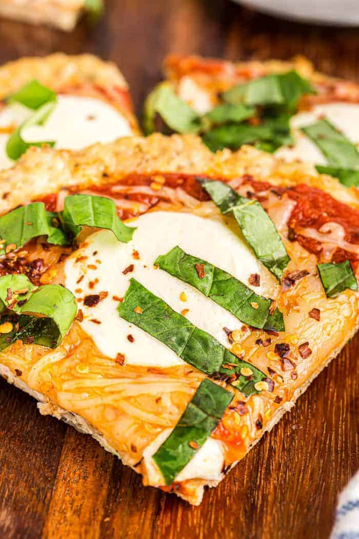 closeup of slice of keto chicken crust pizza covered with fresh basil