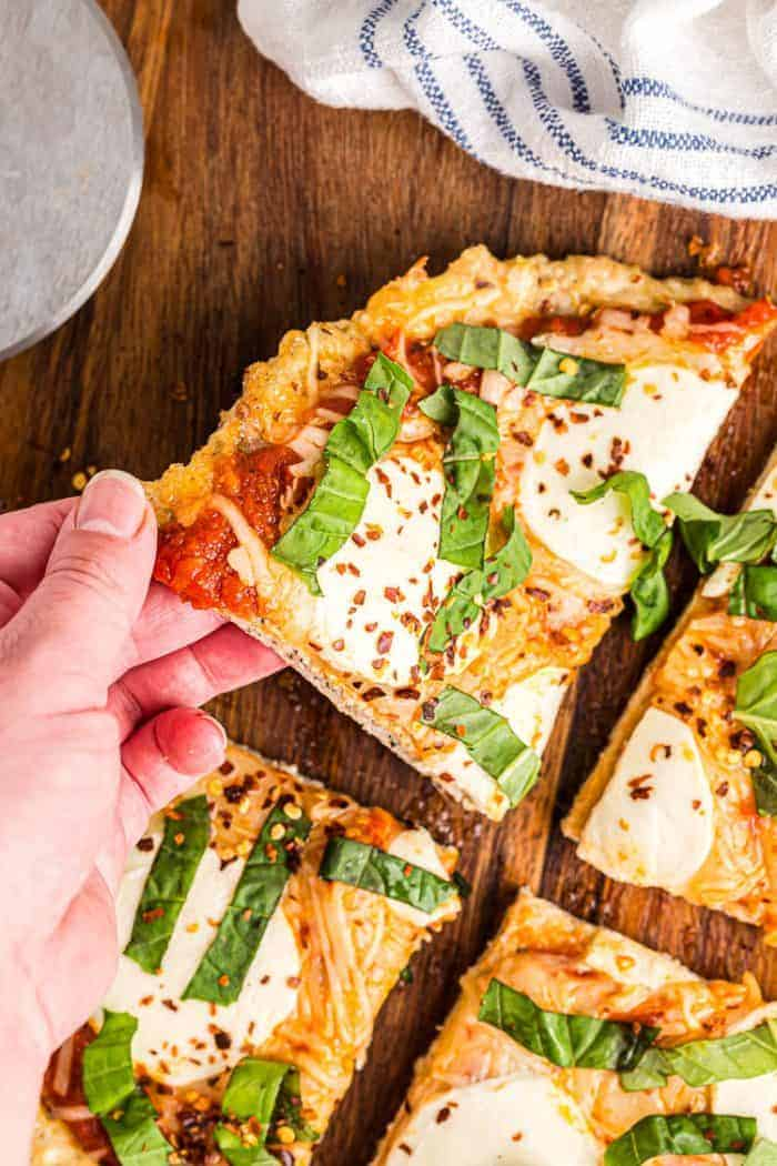 hand reaching out to grab slice of keto chicken crust pizza off cutting board