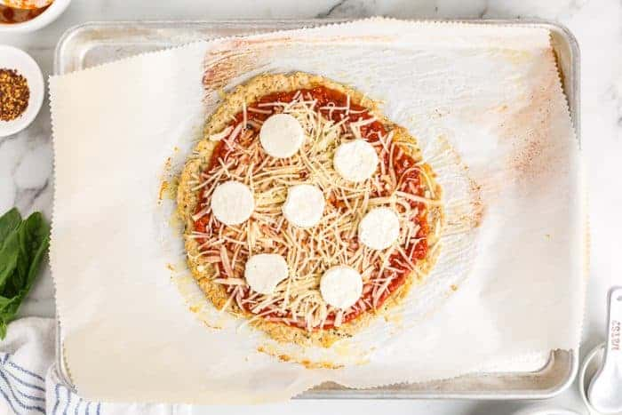 overhead view of uncooked pizza dough with cheese on top