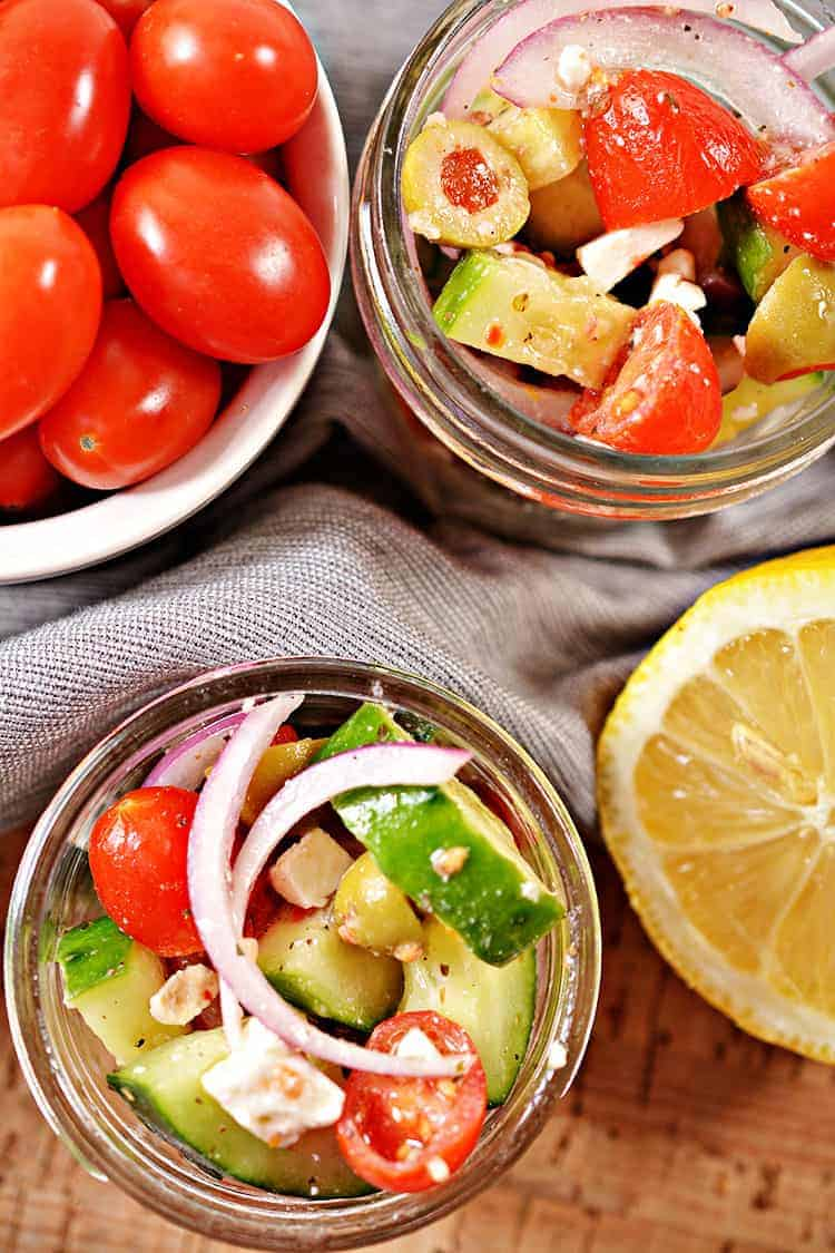 overhead view of keto greek salad in a jar in two small jars next to a lemon