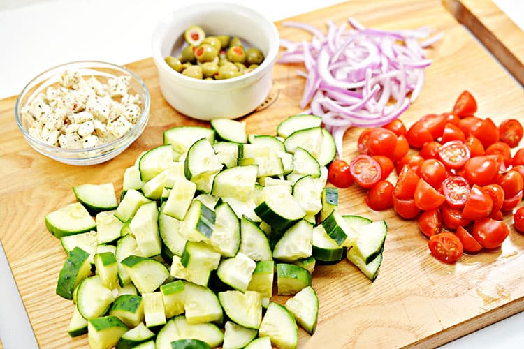 cucumbers, tomatoes, red onions, olives and feta cheese on a chopping board